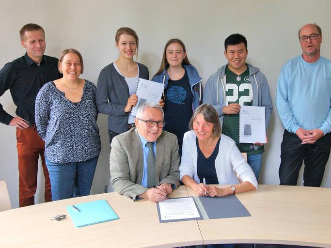 Martin Thunich und Dr. Cornelia Regin (sitzend) bei der Unterzeichnung der Kooperationsvereinbarung.