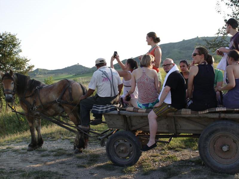 Jugendliche und Kutscher auf einem Holzwagen, der von einem Pferd durch ländliches Gebiet gezogen wird.