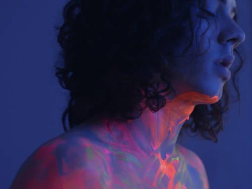 Mann steht in einem abgedunkeltem Raum. Auf seinem Körper leuchten Neon-Farben.