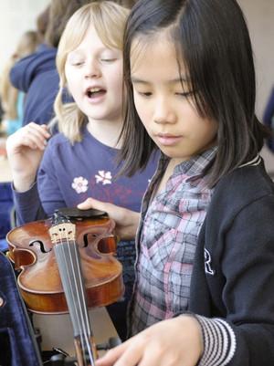 Zwei Mädchen schauen sich eine Violine an.