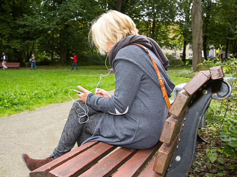 Eine Frau sitzt auf einer Parkbank und lauscht dem Audioguide