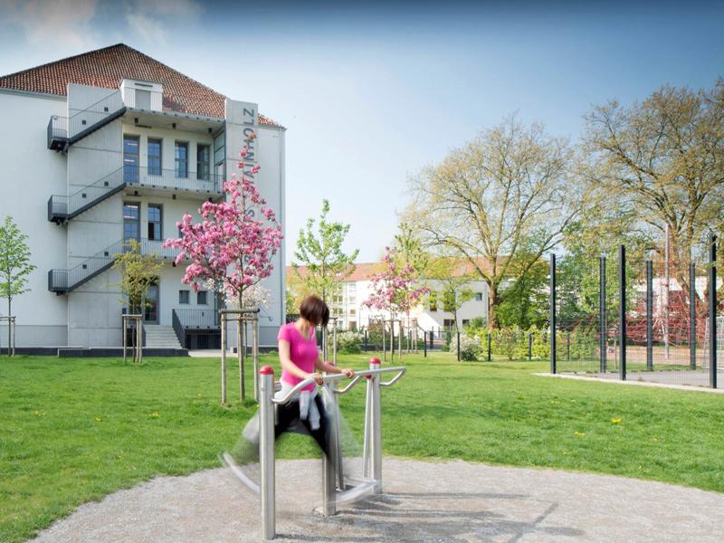 Eine Frau trainiert an einem Fitnessgerät vor blühenden Bäumen