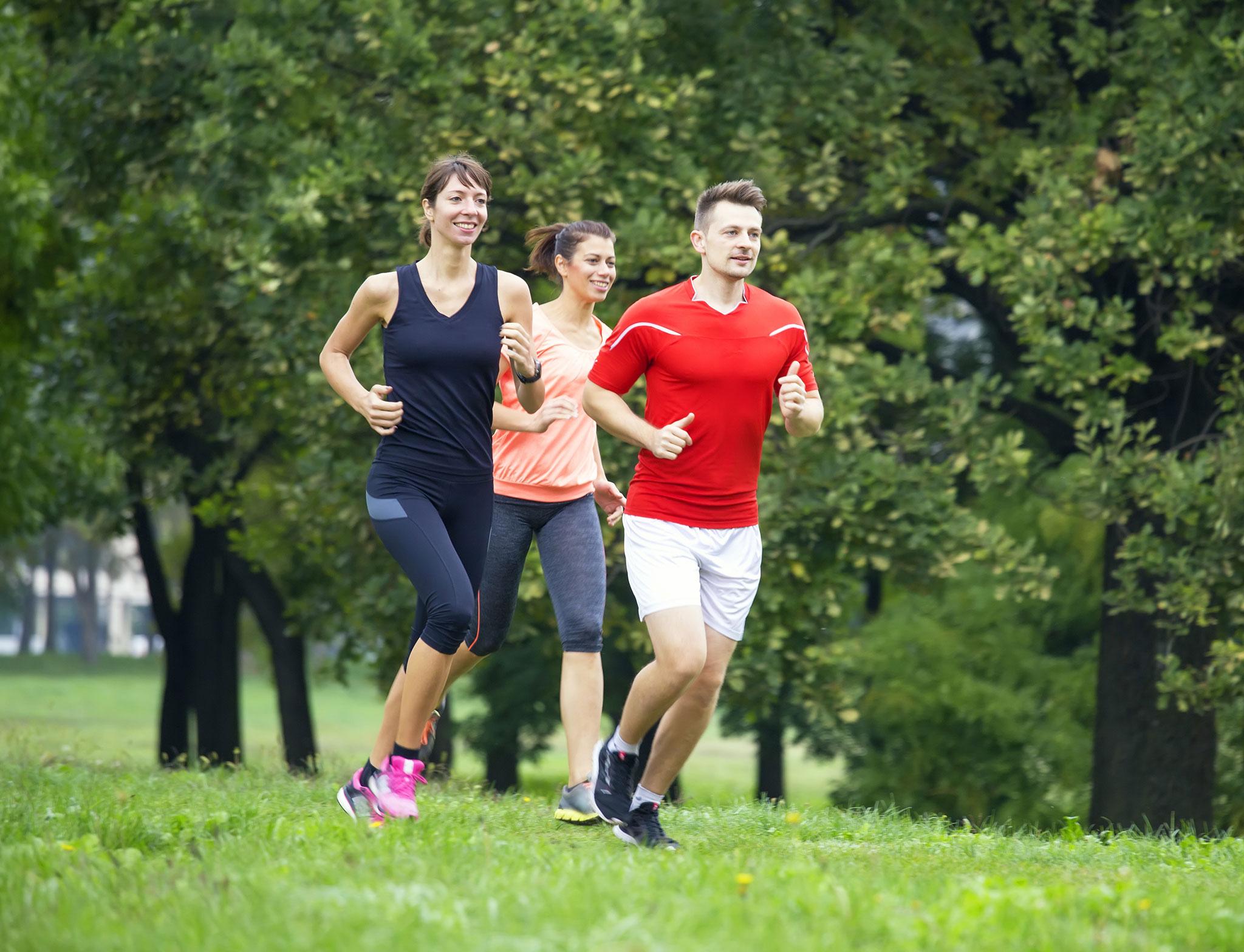 Zwei junge Frauen und ein junger Mann joggen in Sportkleidung durch eine Grünanlage