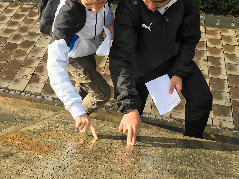Schüler der Wilhelm-Raabe-Schule ertasten am Holocaust-Mahnmal die eingravierten Namen der jüdischen Ermordeten, Oktober 2019