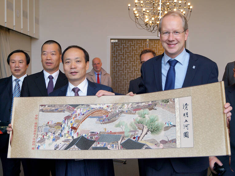 Changde's Lord Mayor Derui Zhou gifts Stefan Schostok with an historical image of his city