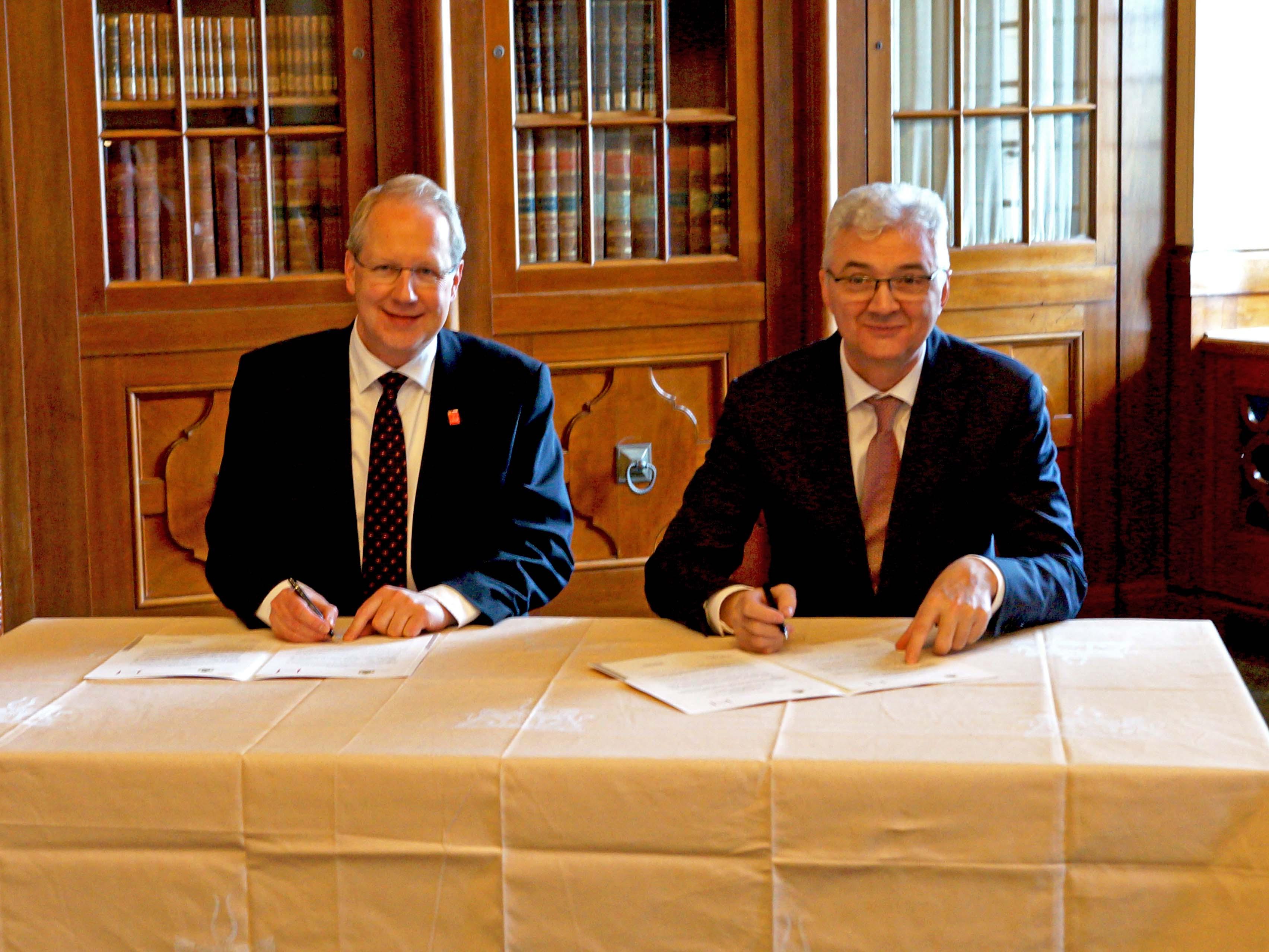 Zwei Männer an einem Schreibtisch.