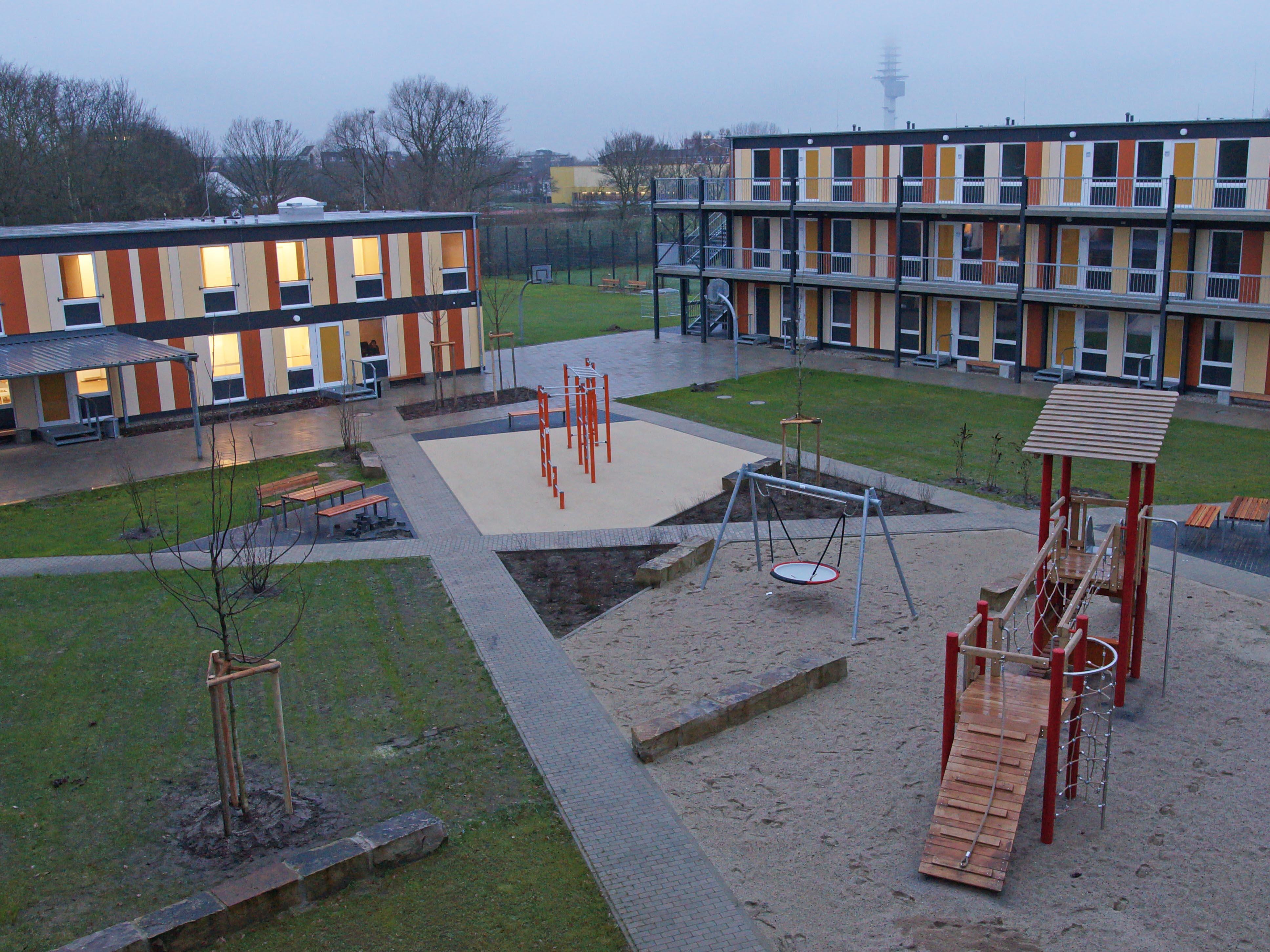 Ein Hof, gesäumt von Gebäuden. Darauf ein Spielplatz.