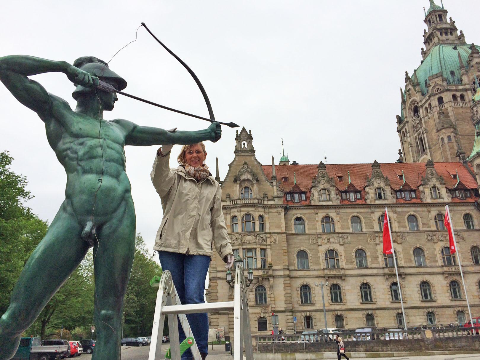 Frau auf einer Leiter, die eine Skulptur berührt.
