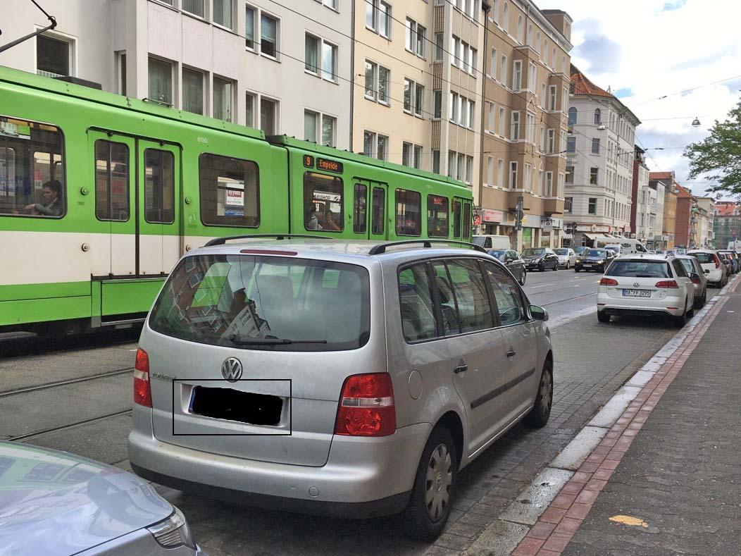 Auto, das auf einem Behindertenparkplatz steht. Im Hintergrund fährt eine Bahn.