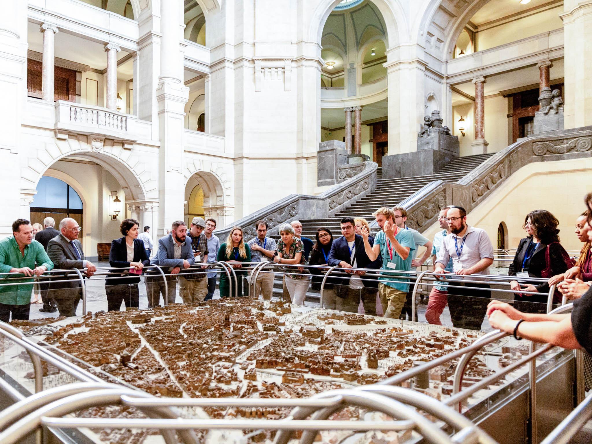 Eine Gruppe Menschen betrachtet das Stadtmodell Hannovers, das die Zerstörungen des Zweiten Weltkriegs dokumentiert