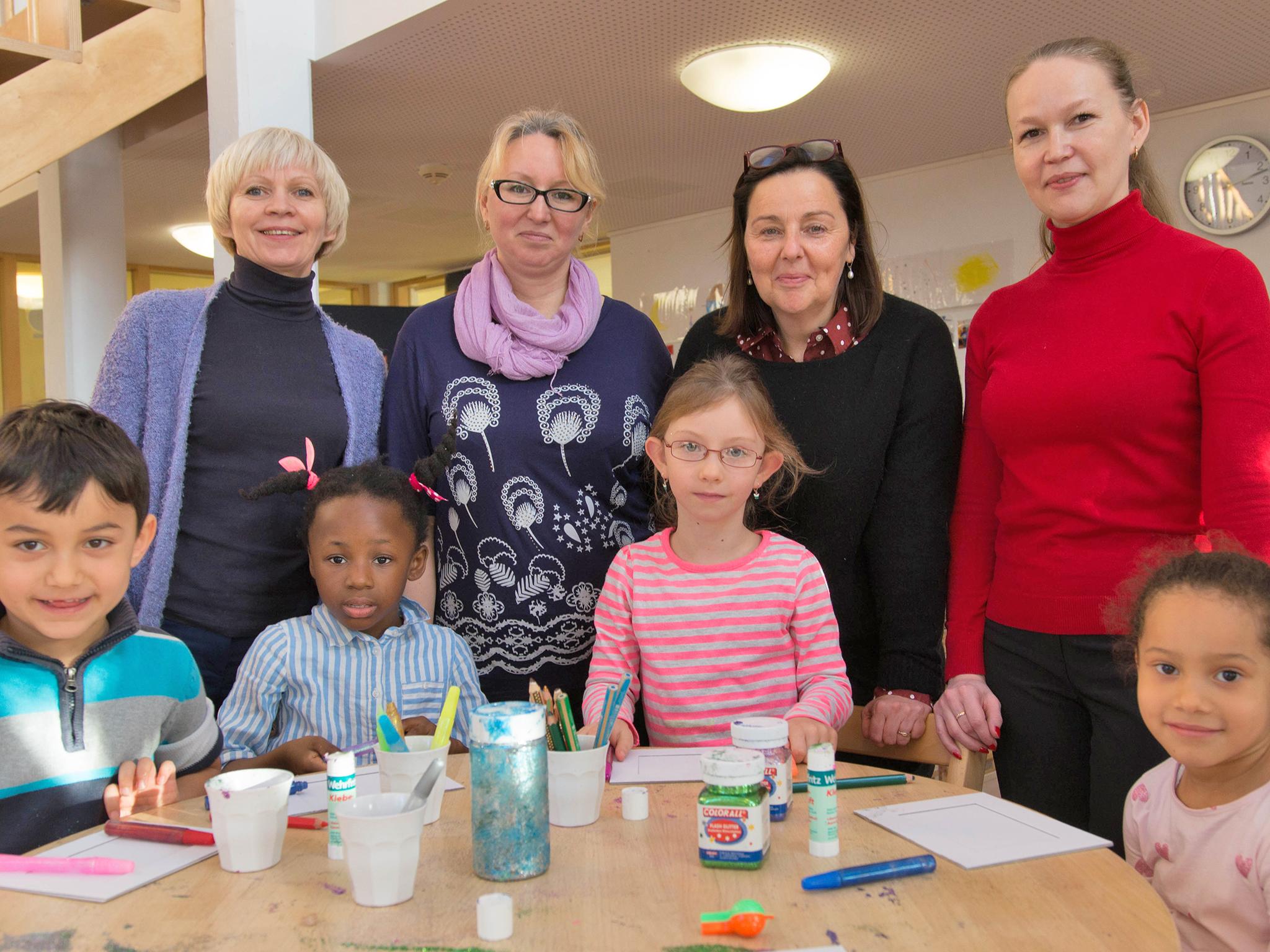 Vier Frauen mit einigen Kindern an einem Tisch.