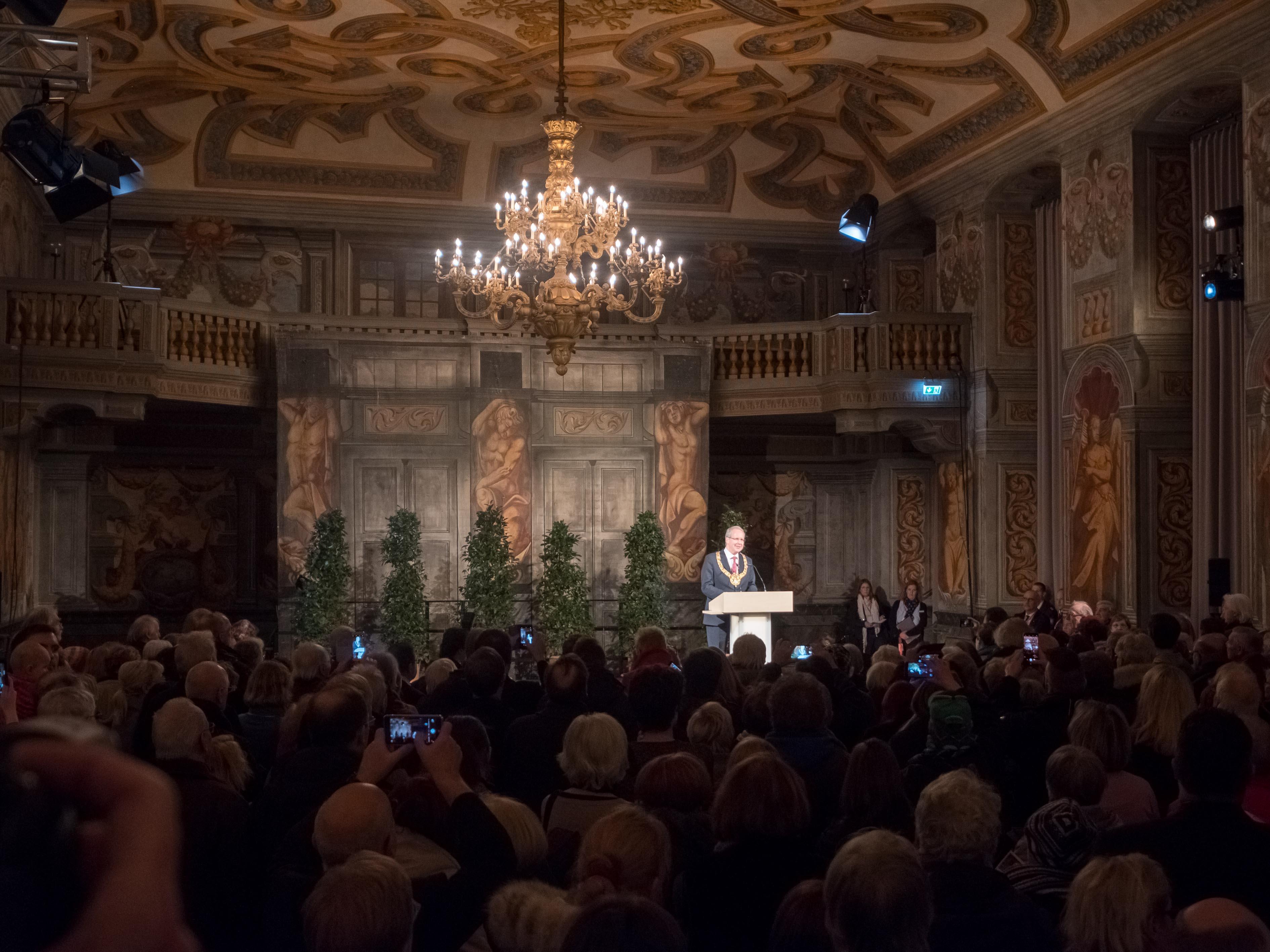 Blick in eine Galerie. Auf der Bühne steht ein Mann, der zu zahlreichen Besucherinnen und Besuchern spricht.