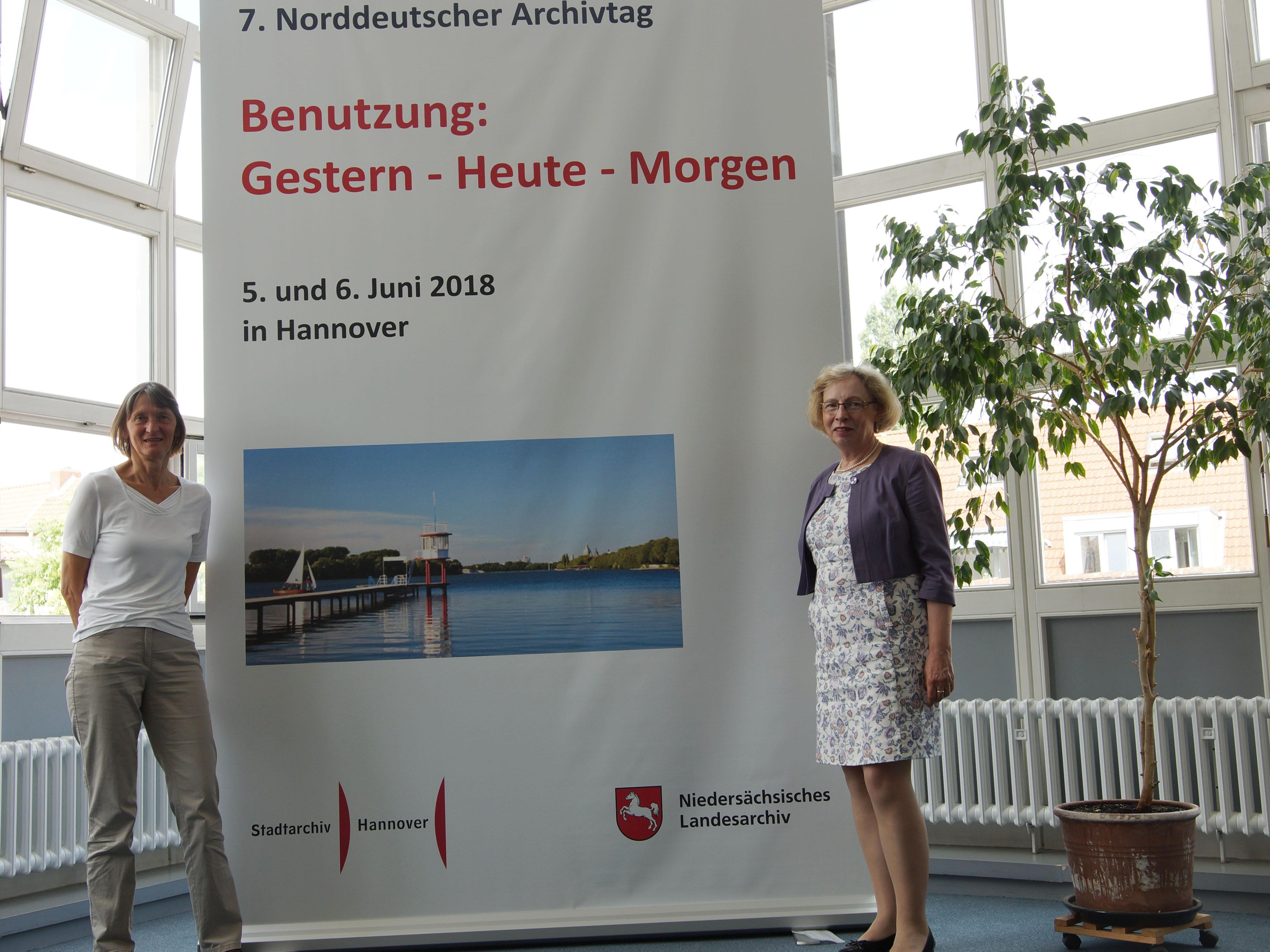 Zwei Frauen neben einem Plakat