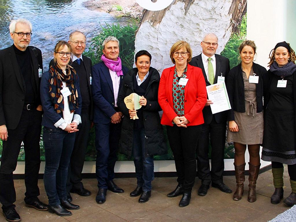 Gruppenaufnahme von neun Personen, wobei zwei Auszeichnungen in Händen halten.