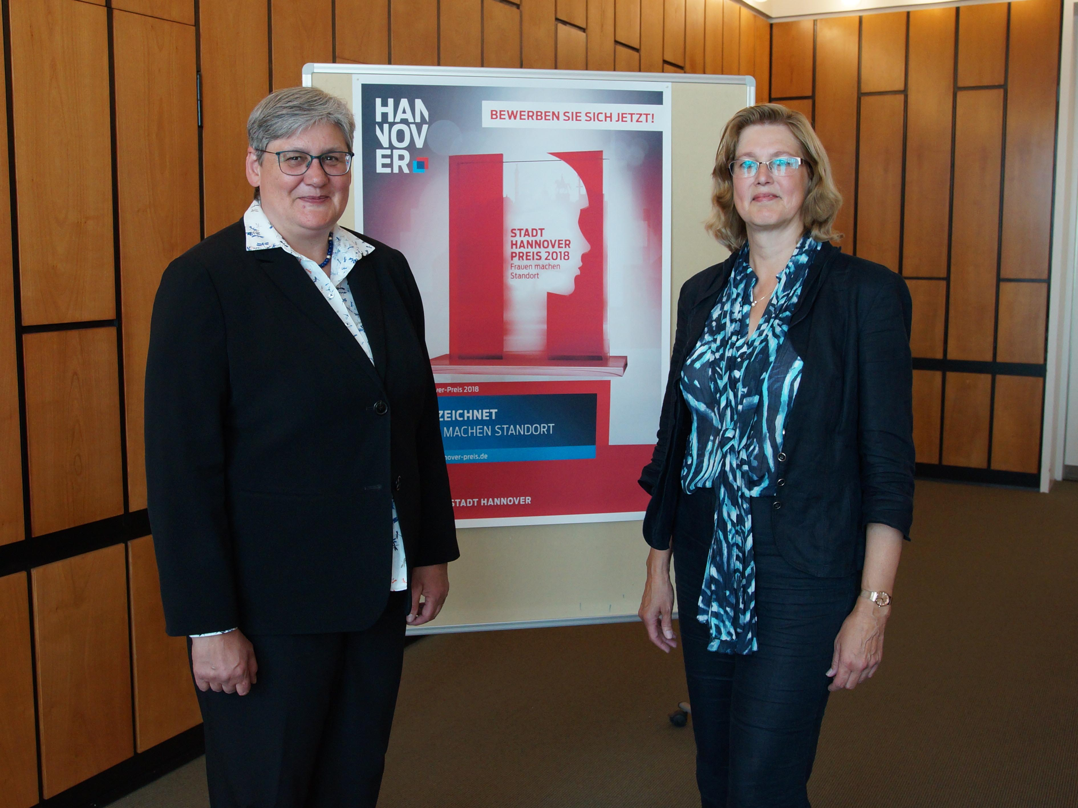 Zwei Frauen vor einem Plakat.