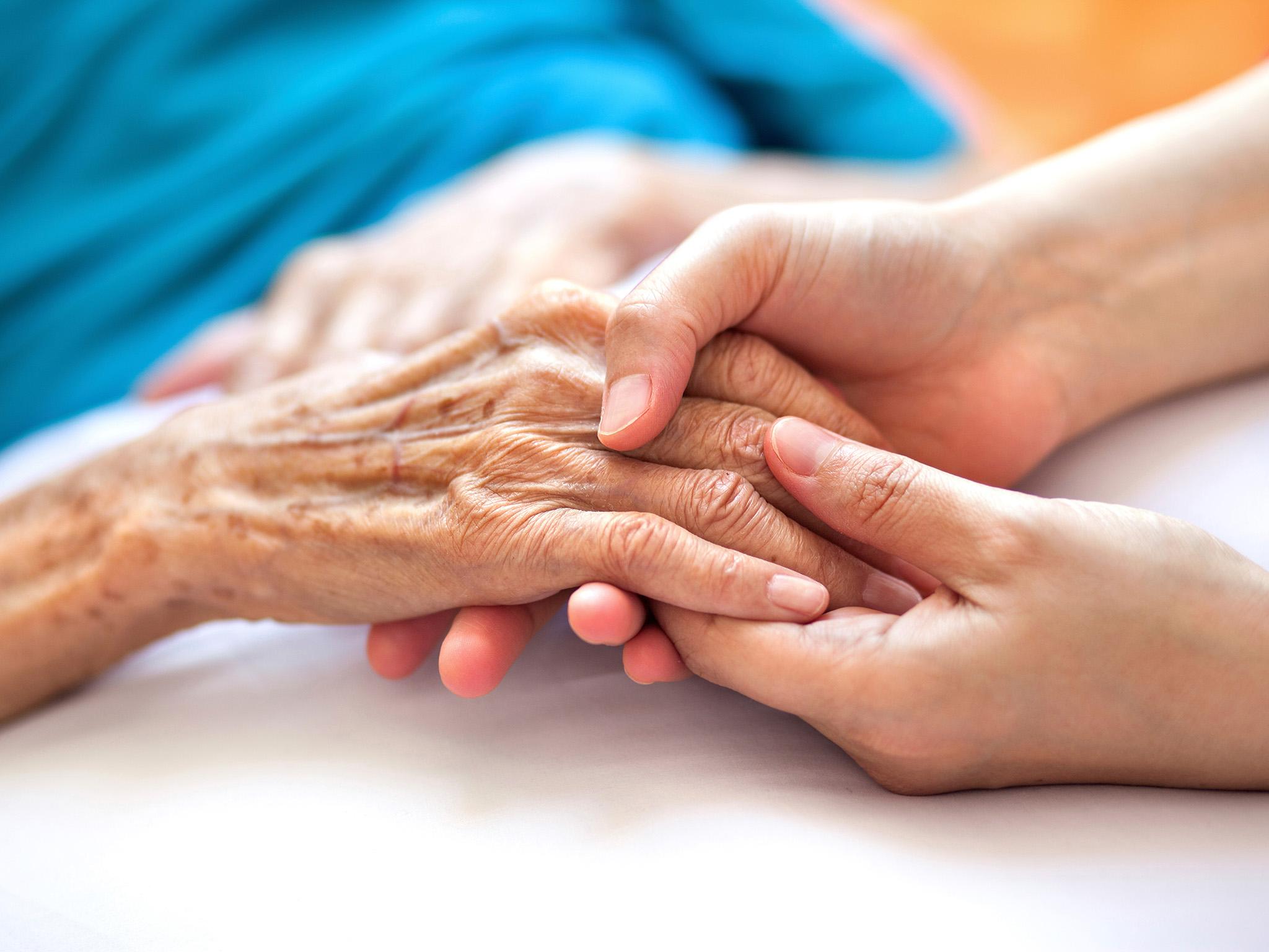 Zwei Hände eines jungen Menschen halten die Hand einer älteren Person