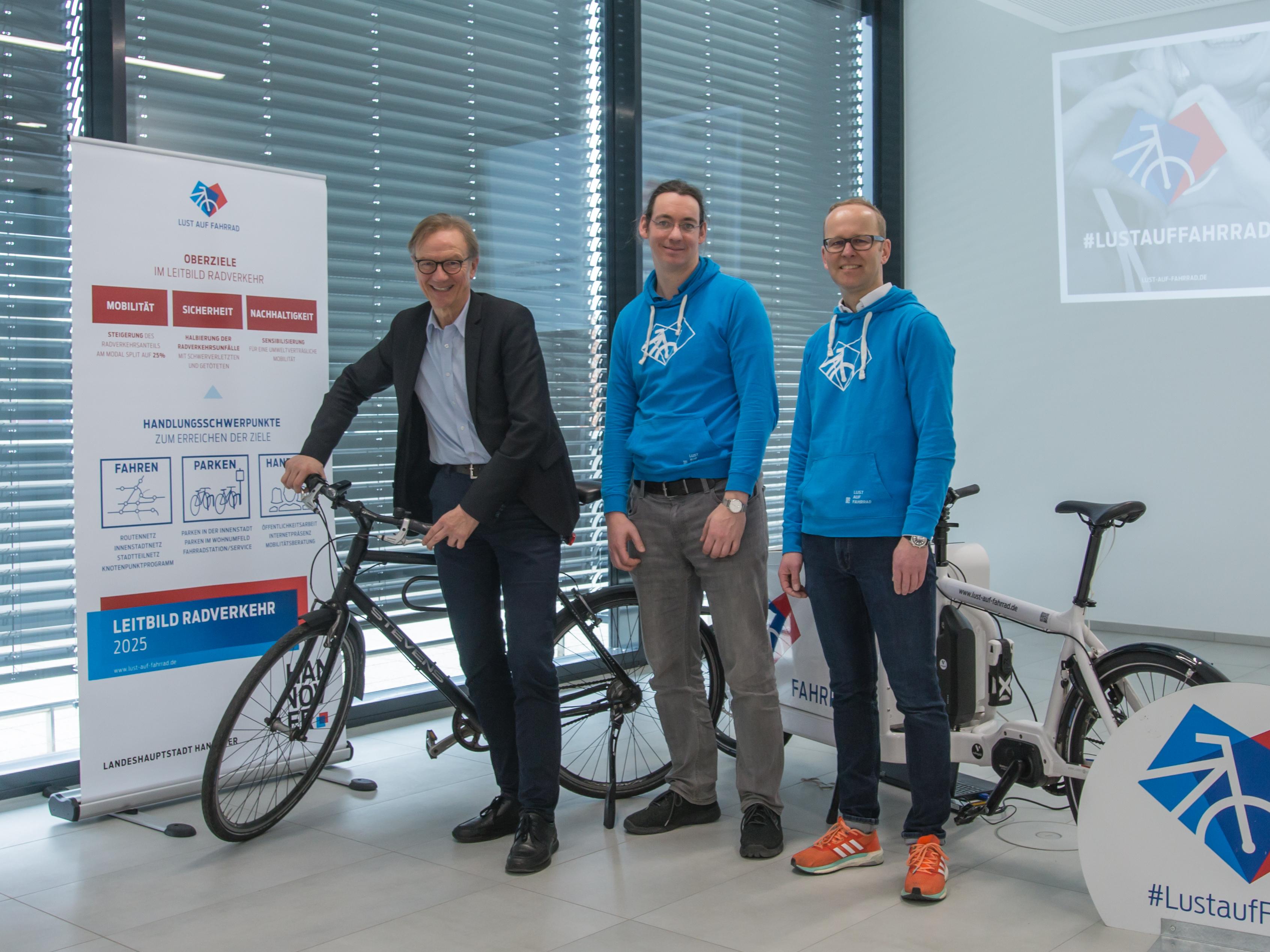 Drei Männer mit einem Fahrrad in einem Saal.