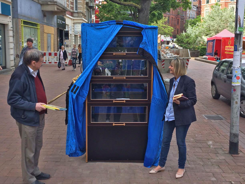 Ein Mann und eine Frau vor einem Bücherschrank.