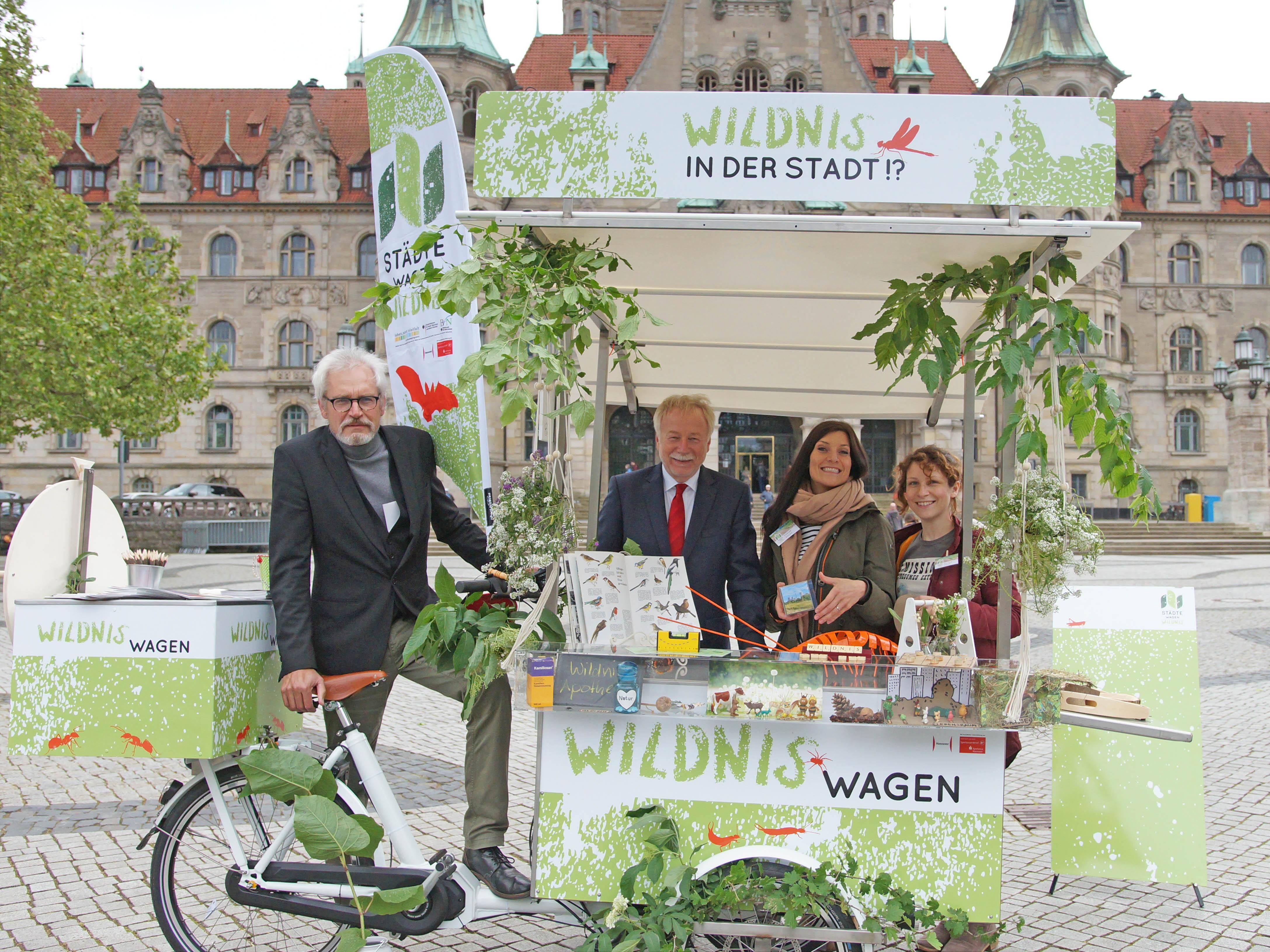 Zwei Männer und zwei Frauen vor und hinter einem pflanzenverzierten Lastenrad.