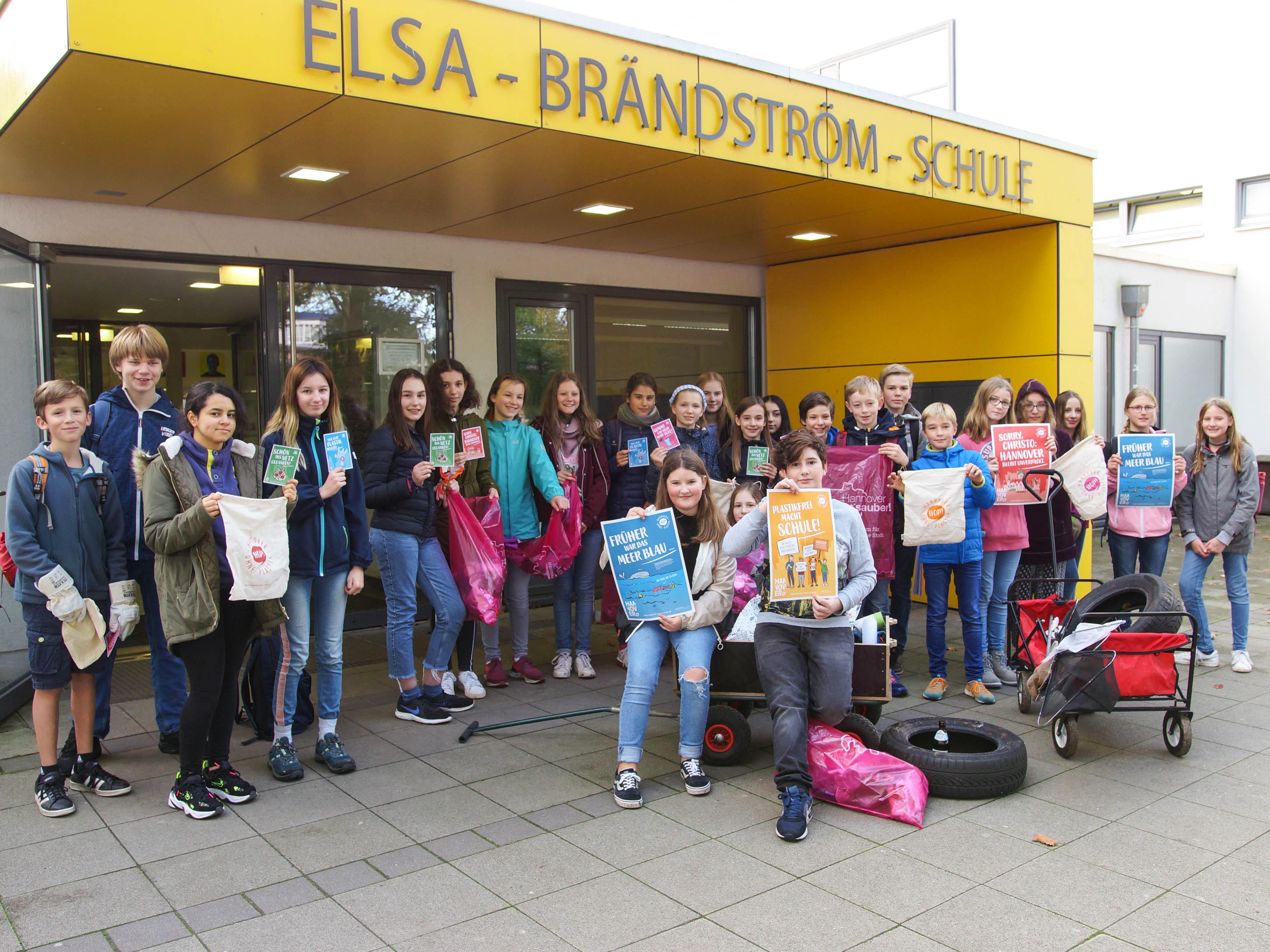 Schulklasse vor einem Schulgebäude. Einige halten Plakate.