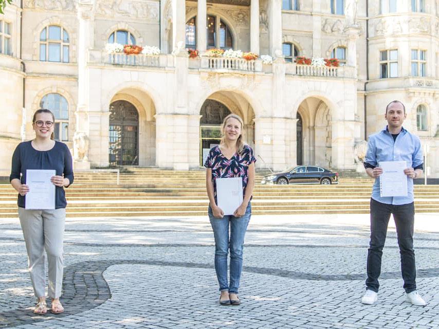 Drei junge Menschen vor einem Rathaus. Sie halten ein Abschlusszeugnis.