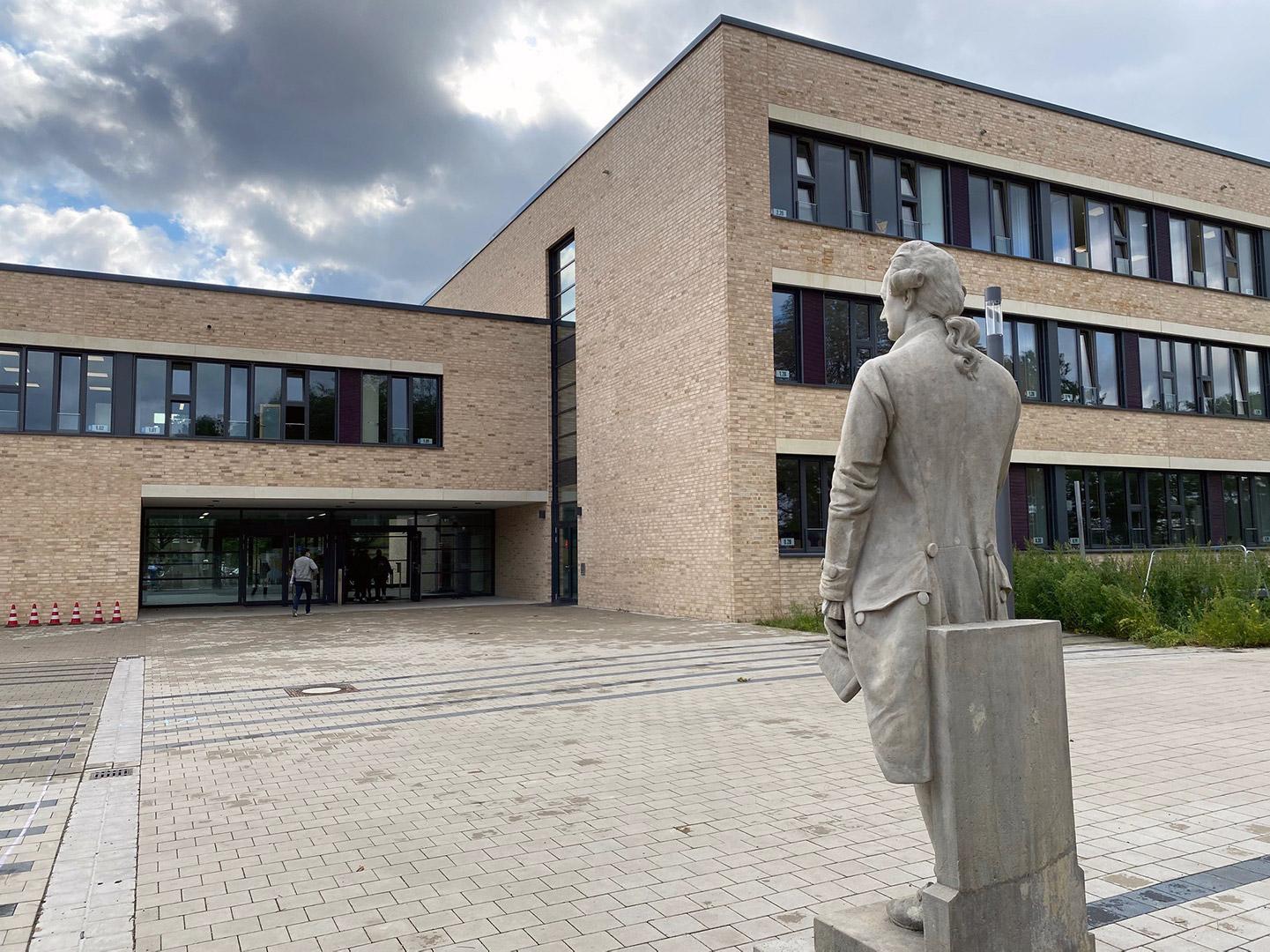 Ein modernes Schulgebäude, rechts davor eine Statue.