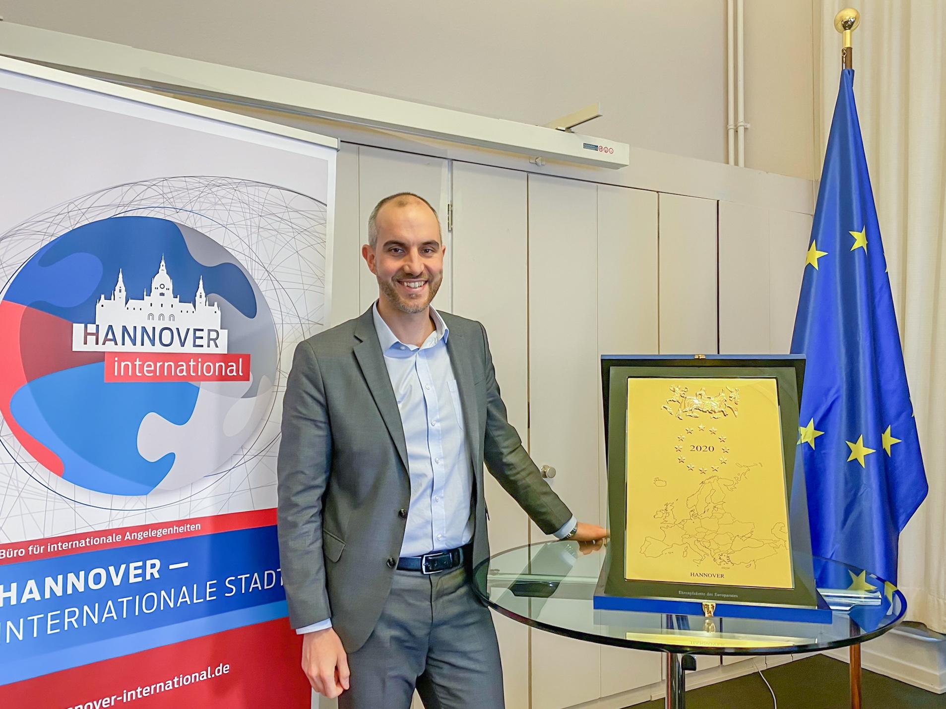 """Belit Onay steht an einem Tisch, auf dem die Ehrenplakette des Europarates steht, daneben die Flagge der EU und ein Aufsteller mit der Aufschrift """"Hannover – Internationale Stadt"""""""