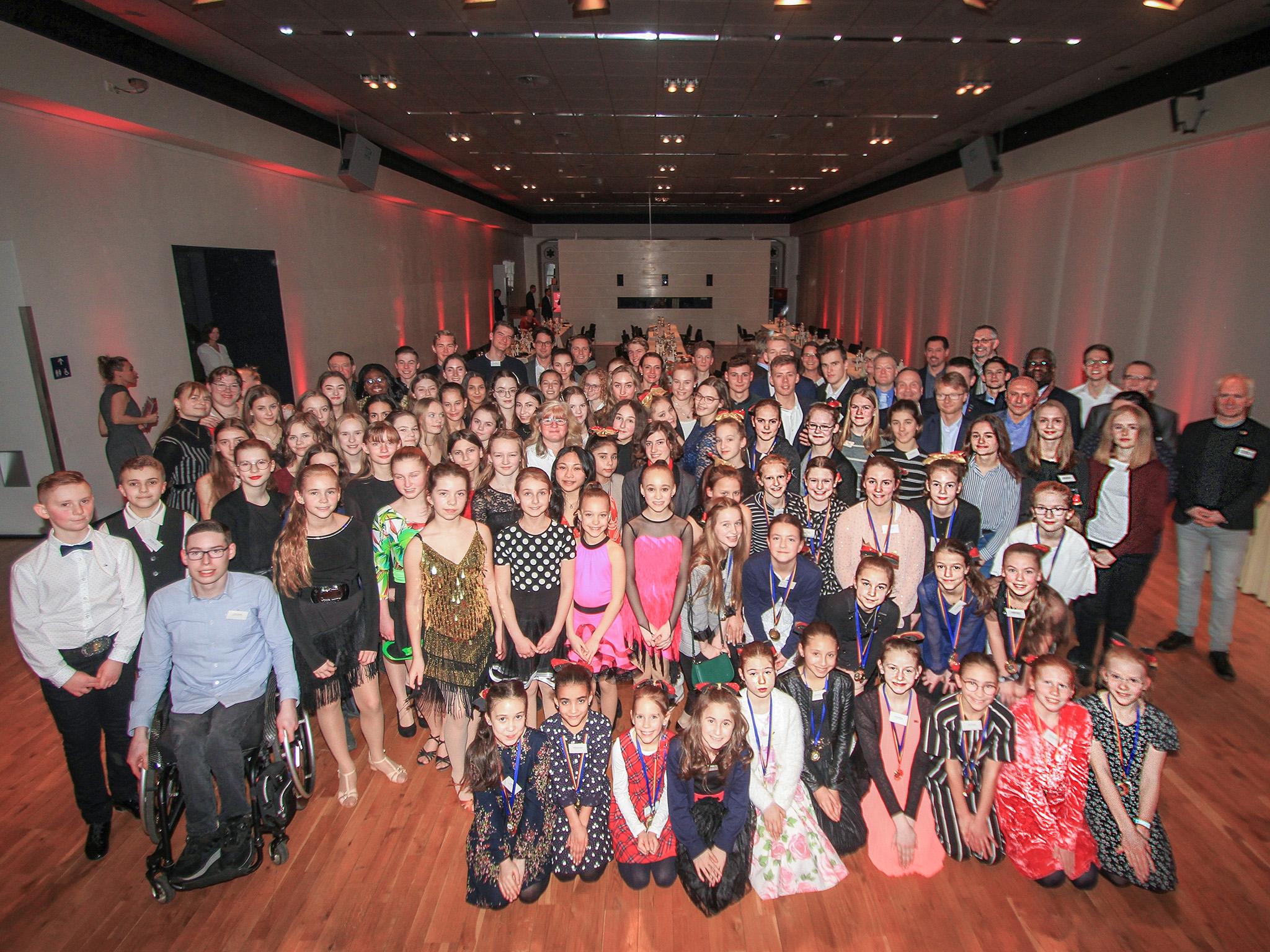 Eine große Gruppe junger Menschen in einem Saal
