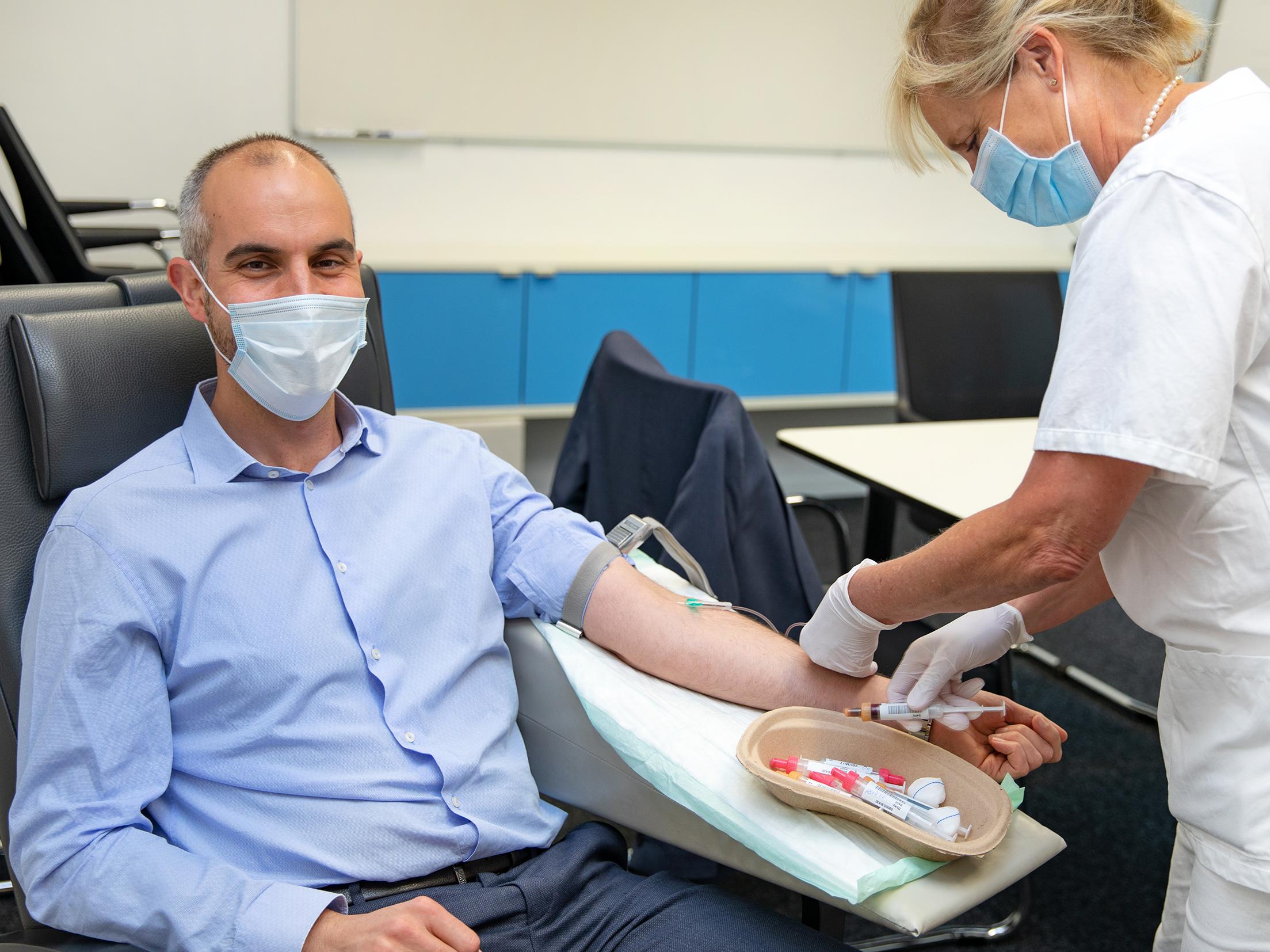 Mann mit Mundschutz, dem von einer Frau mit Mundschutz Blut abgenommen wird.