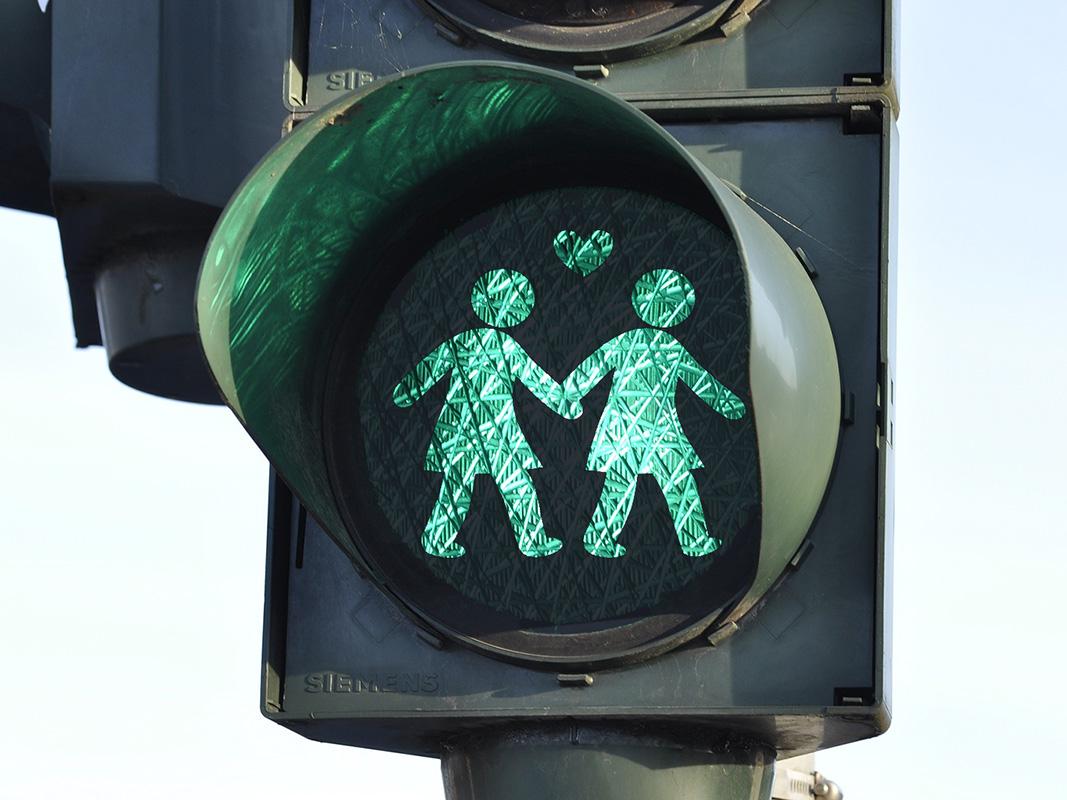 Ampel mit einem grünen Ampelzeichen, das zwei Frauen zeigt, die sich an den Händen halten.