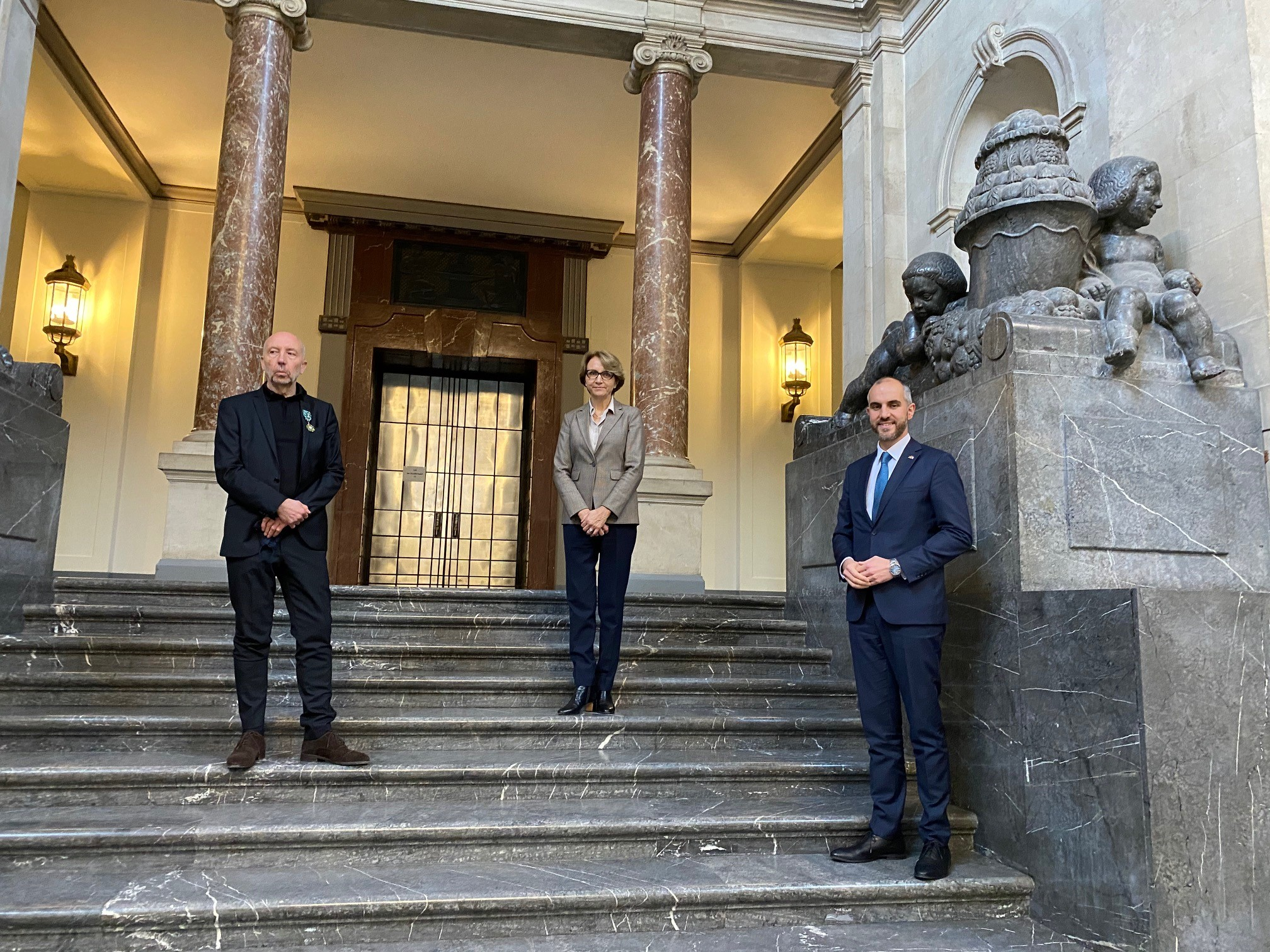 Drei Personen auf einer Treppe.