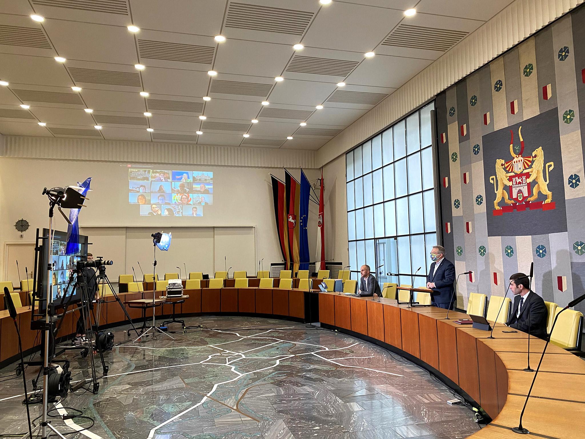 Ein Plenarsaal mit Videotechnik, am rechten Rand drei Personen.