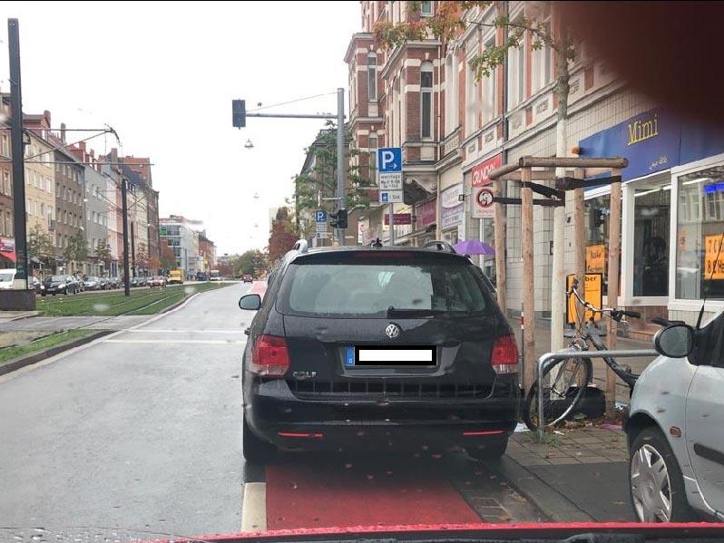Ein Auto, das auf einem Radweg steht.