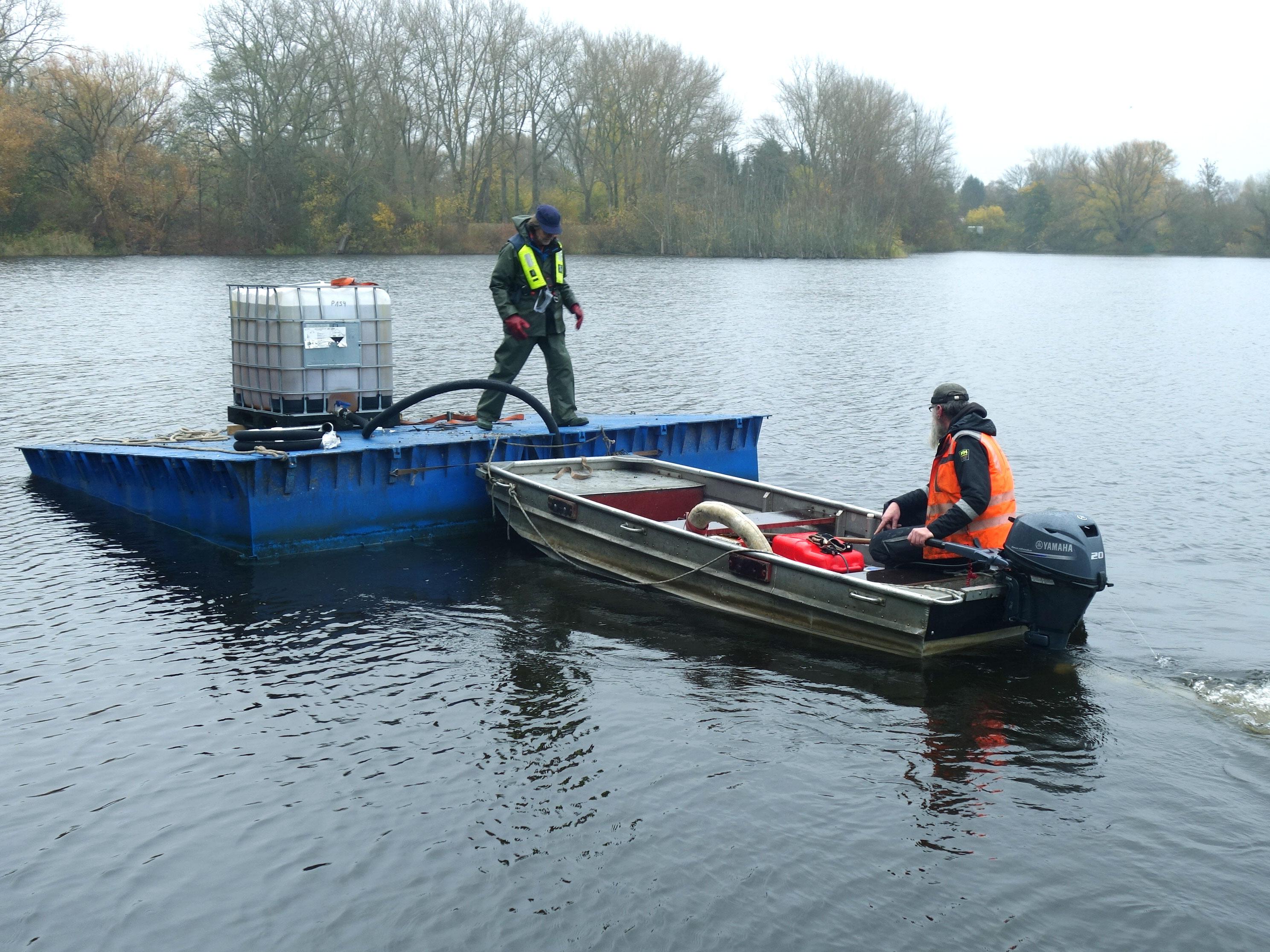 Das Fällmittel wird von einem Boot aus über einen Schlauch ausgebracht und gleichmäßig im Siebenmeterteich verteilt.