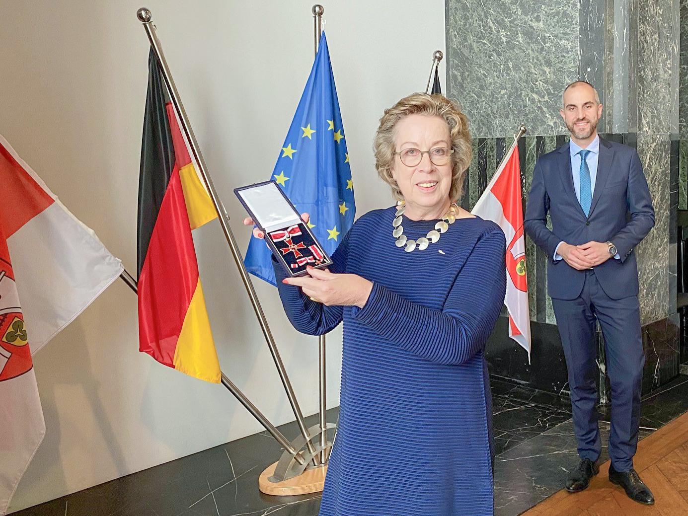 Mechthild Schramme-Haack und Oberbürgermeister Belit Onay in einem Saal. Frau Schramme-Haack hält den Verdienstorden. Im Hintergrund vier Flaggen.