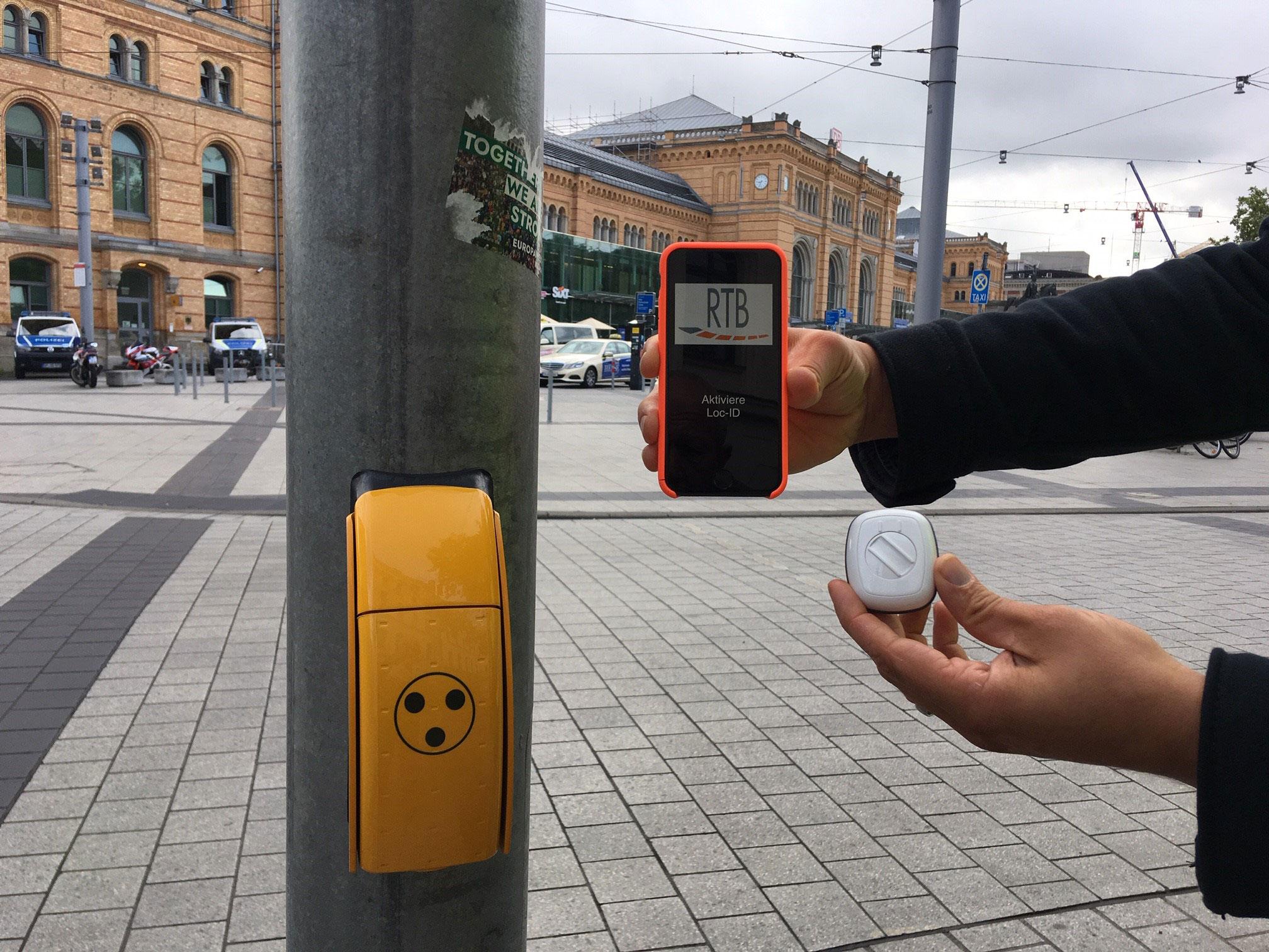 Sender mit Druck-Knopf und ein Smartphone mit LOC.id-App