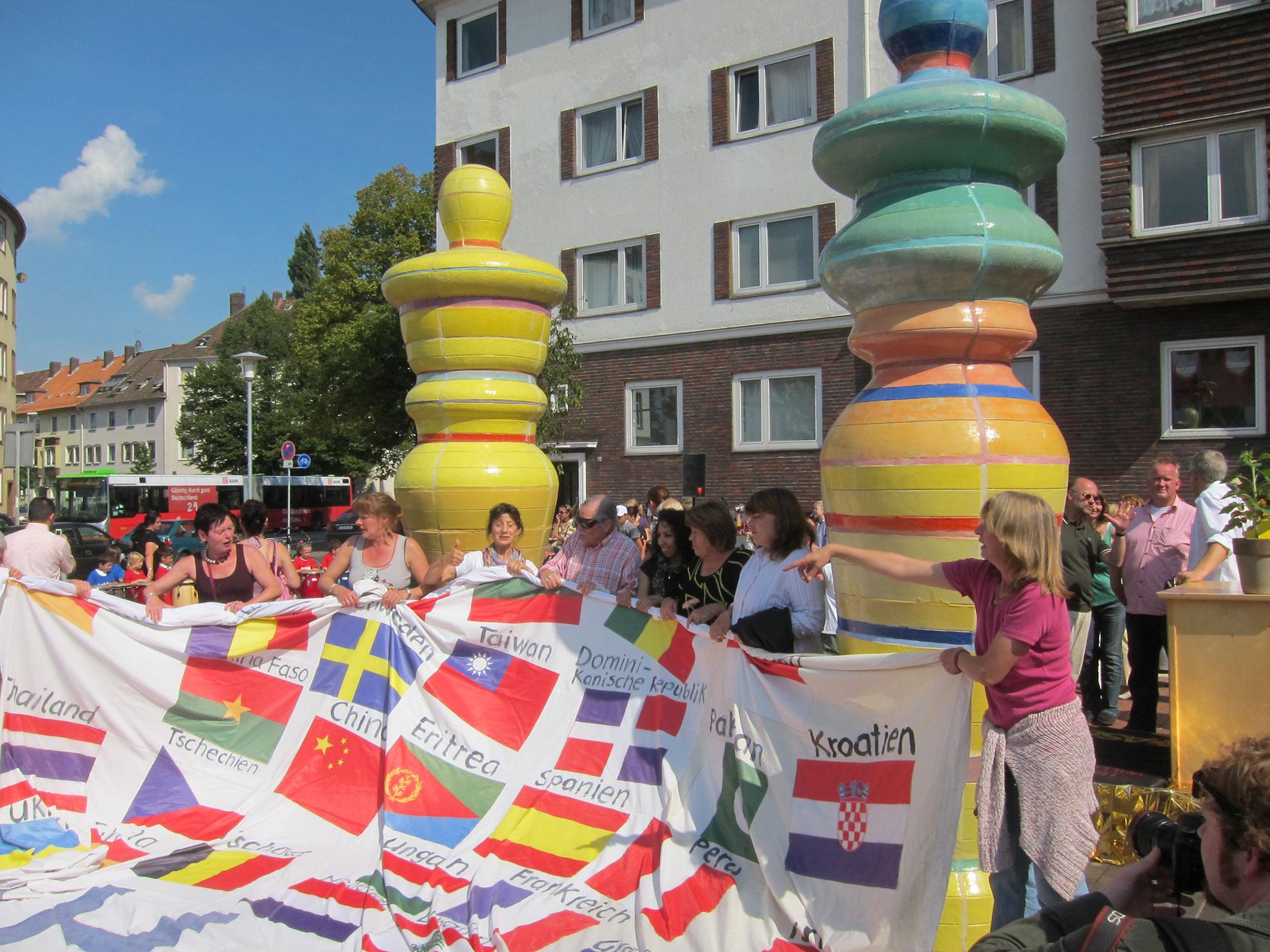 Mehrere Personen halten ein großes Banner, auf dem zahlreiche Nationalflaggen abgebildet sind.