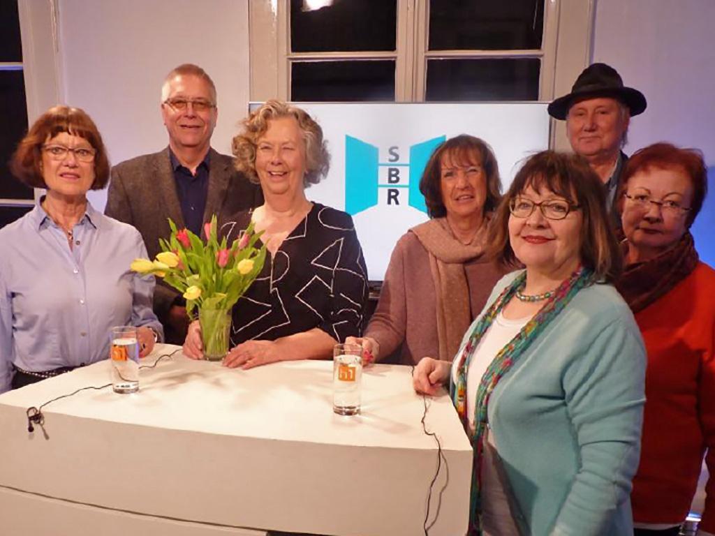 Gruppenaufnahme mit sieben Personen, die an einem Moderationstisch in einem Studio stehen; dahinter das Logo des Seniorenbeirats der Landeshauptstadt Hannover.