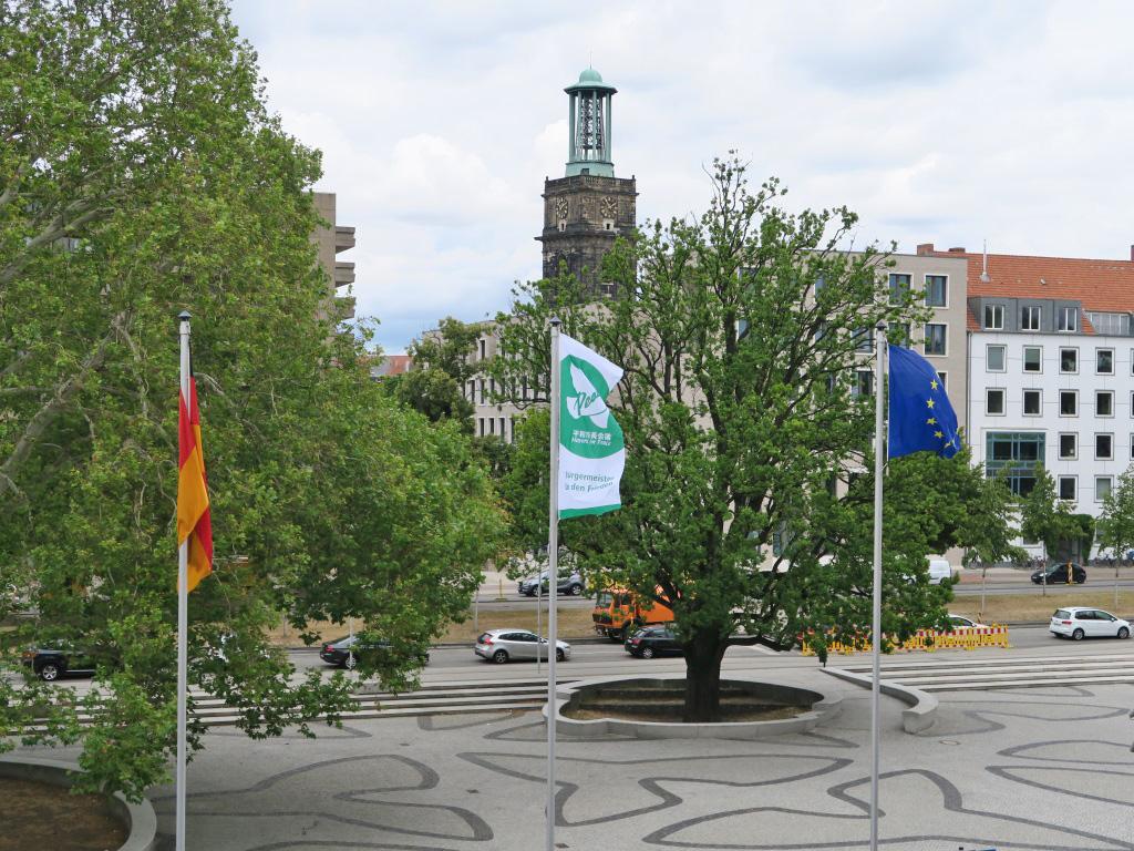 Auf dem Rathausvorplatz weht zwischen der Deutschlandflagge und der Europaflagge die Flagge der Bürgermeister für den Frieden mit einer weißen Friedenstaube