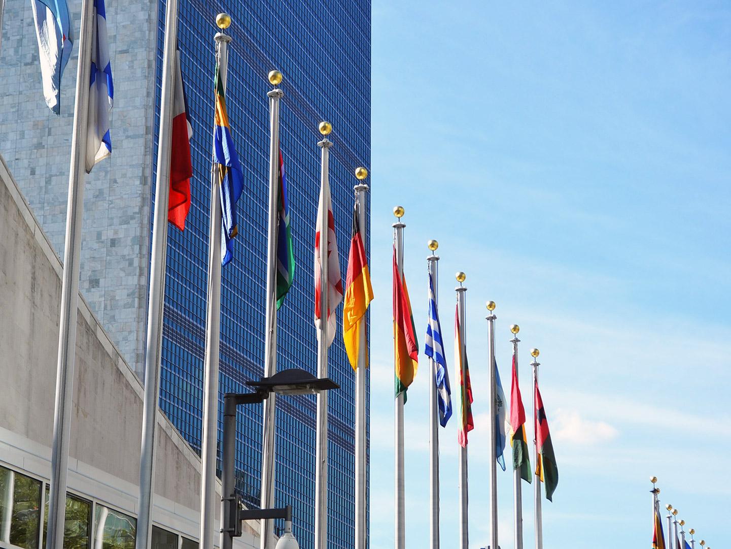 Flaggen verschiedener Nationen vor einem hohen Gebäude
