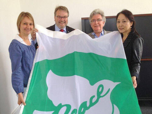 Evelyn Kamissek (Office for International Affairs), Mayor Thomas Hermann, Michel Cibot and Miho Cibot (l. to r.) with the flag of Mayors for Peace