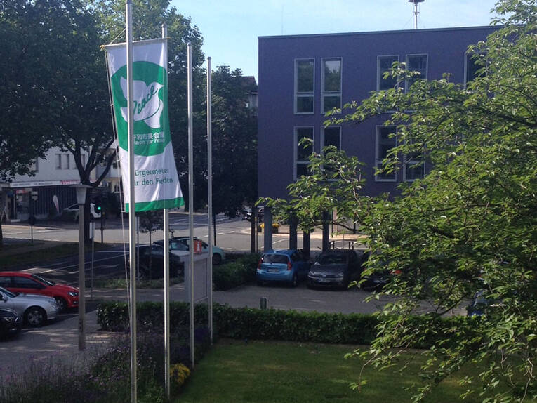 Flagge von Mayors for Peace hängt am Fahnenmast in Neu-Isenburg