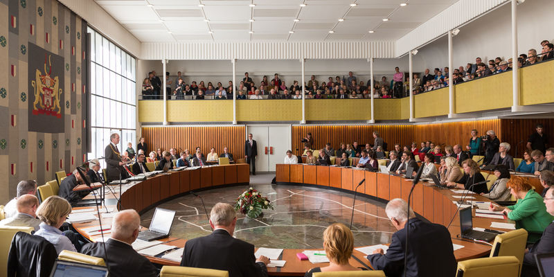 The Lord Mayor addresses the councillors in the council hall, while spectators watch him from the gallery