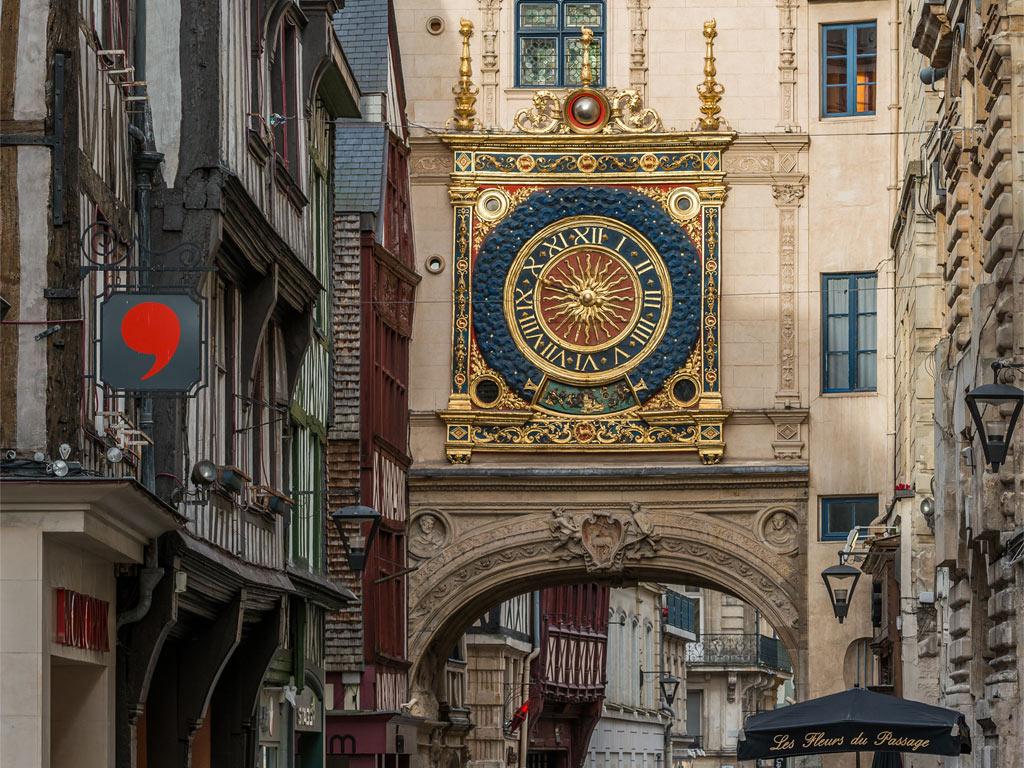 Eine übergroße, reich verzierte antike Wanduhr an einem alten Haus in Rouen