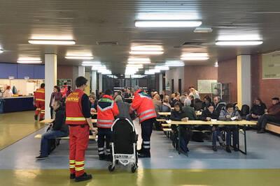 Helfer unterstützen die Evakuierten, die an Holztischen sitzen.