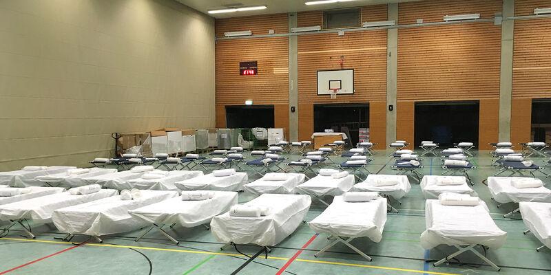 Mehrere Reihen von Feldbetten sind in einer Sporthalle aufgebaut