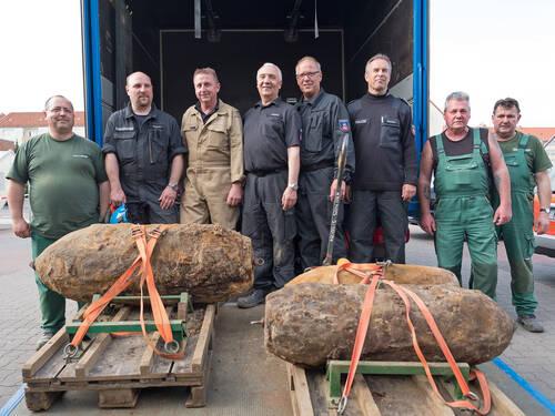 Acht Männer mit drei entschärften Bomben.