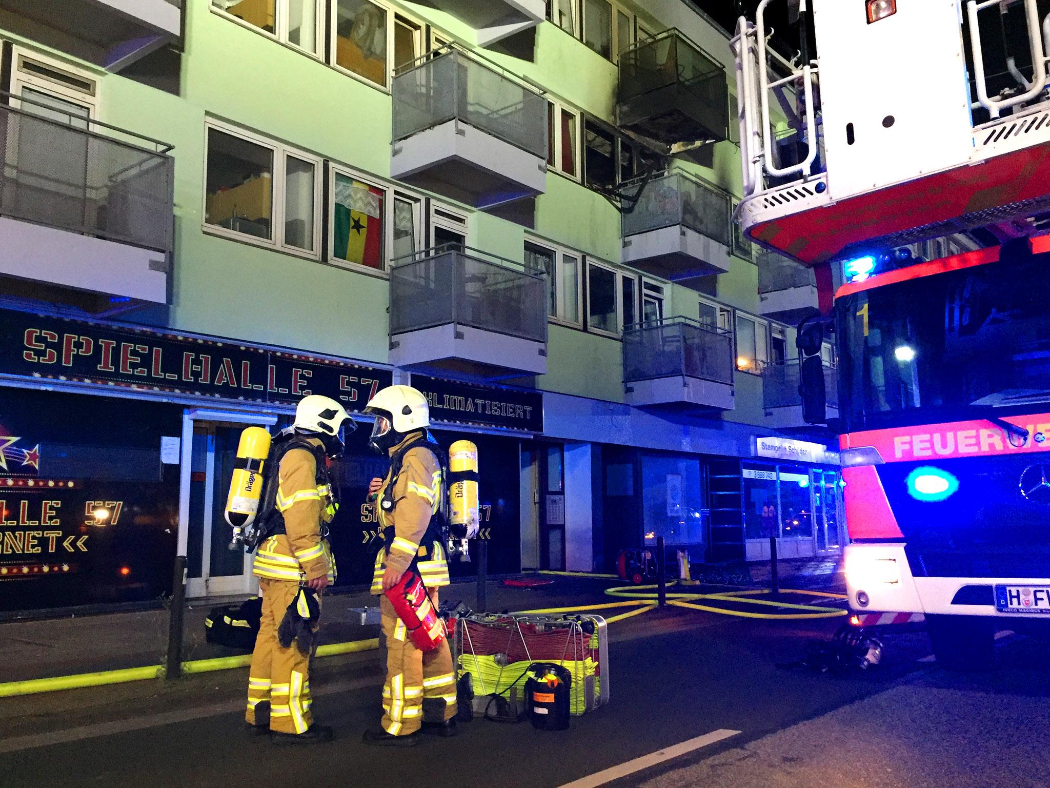 Zwei Einsatzkräfte mit angelegtem Atemschutz. Im Hintergrund der ausgebrannte Balkon der betroffenen Wohnung.