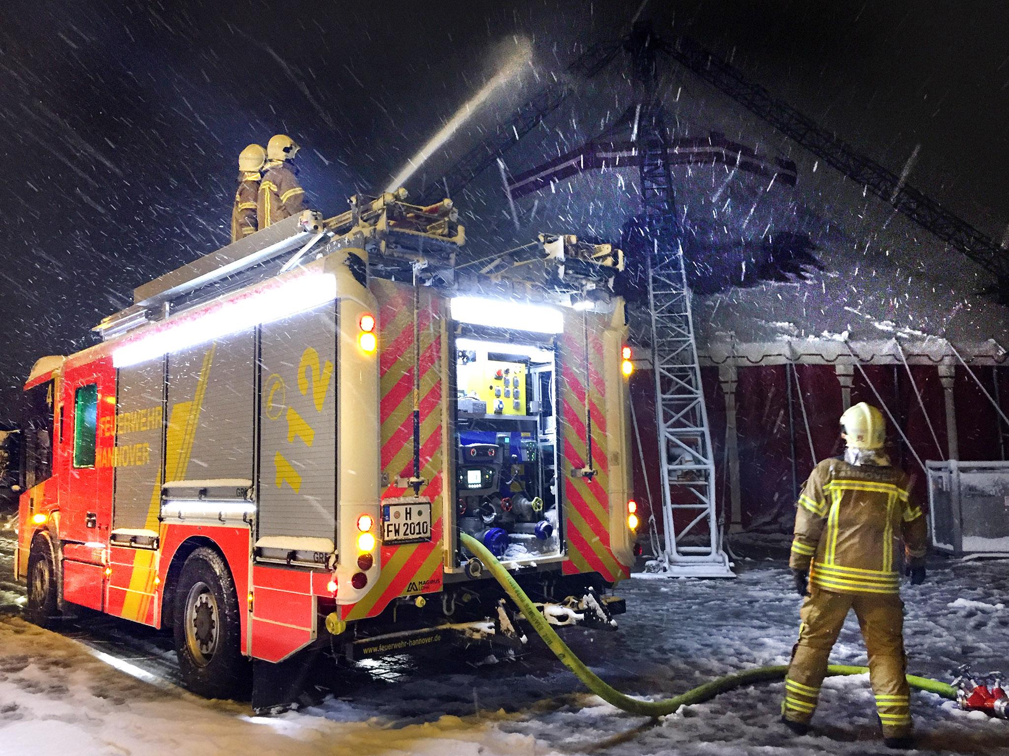Im Vordergrund ein HLF20 der Feuerwehr Hannover mit mehreren Einsatzkräften, die durch Spülen das Zirkuszelt im Hintergrund von der Schneelast befreien.