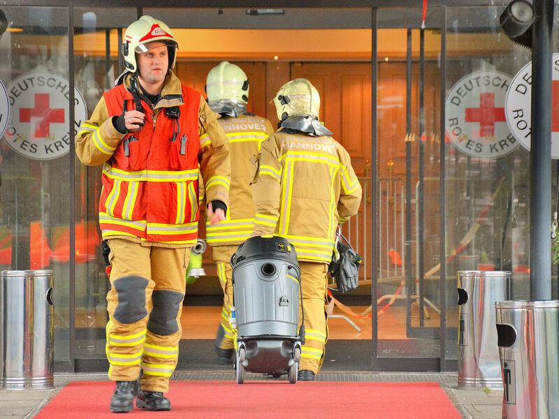 Mehrere Einsatzkräfte der Feuerwehr Hannover mit technischem Gerät, beim Betreten und Verlassen der Flüchtlingsunterkunft am Friedrichswall.